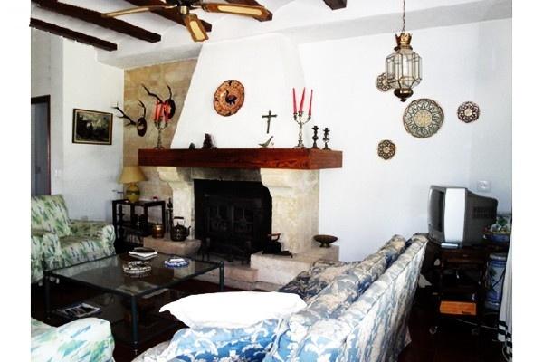Das großzügige Wohnzimmer mit offenem Kamin, dekoriert mit vielen liebevollen Details
