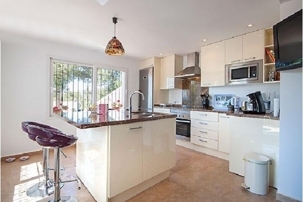 Die große, exzellente Küche mit Kücheninsel und direktem Zugang zur Terrasse