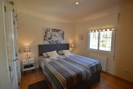 Schlafzimmer mit Doppelbett und großem Einbaukleiderschrank