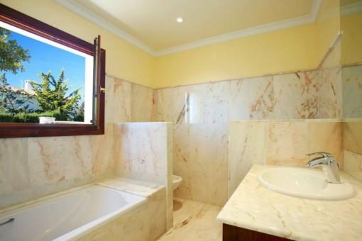 Hauptschlafzimmer mit Badewanne und Tageslicht