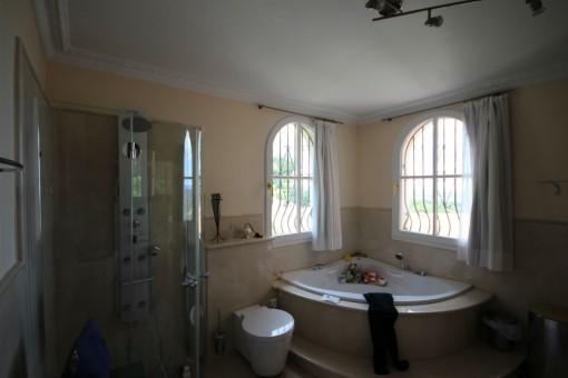 Lichtdurchflutetes Badezimmer mit Wellnessdusche und Eckbadewanne